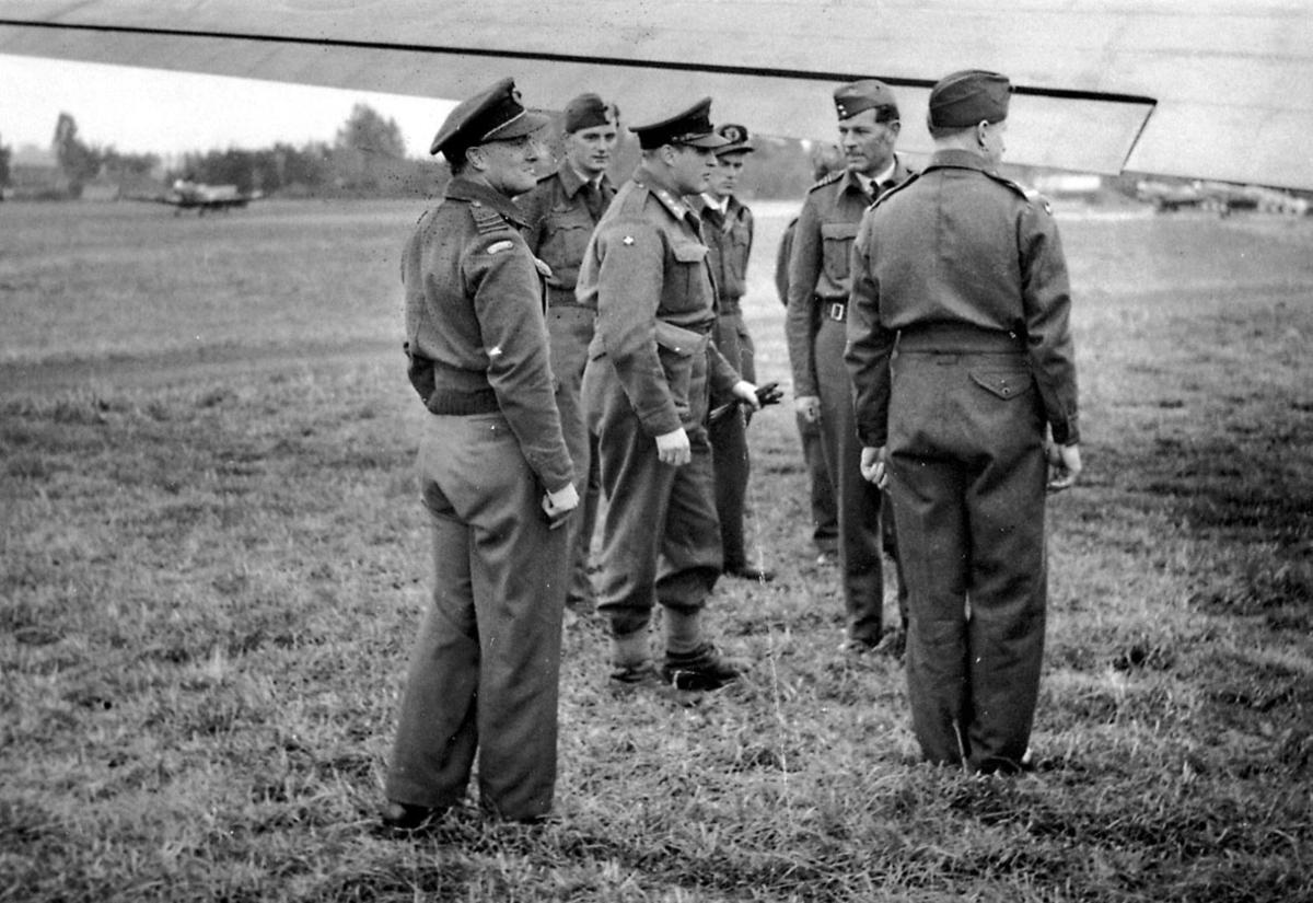 7 personer i militæruniform. Kronprins Olav sammen med 6 andre, på en åpen plass, under en flyvinge. Noen fly i bakgrunnen.