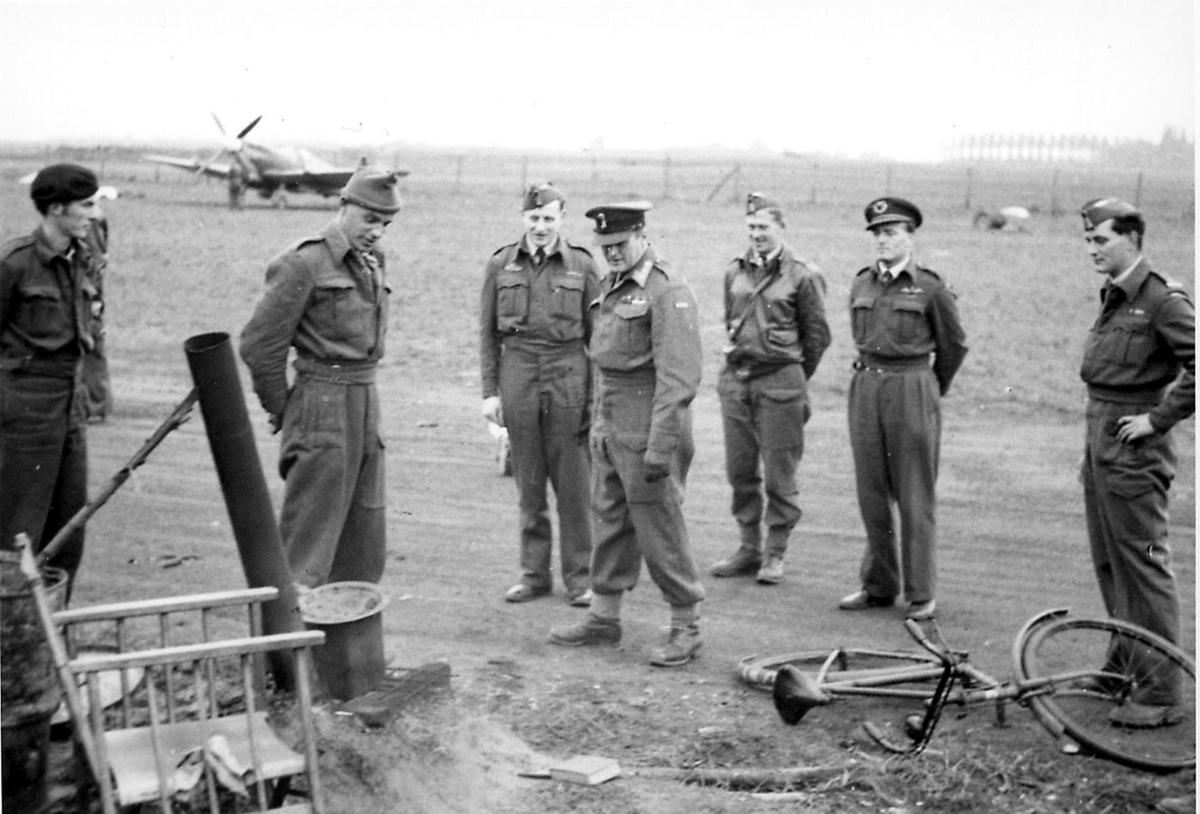 7 personer i militæruniform. Kronprins Olav og 6 andre,  på en åpen plass. Fly i bakgrunnen. Sykkel og div. i forgrunnen.