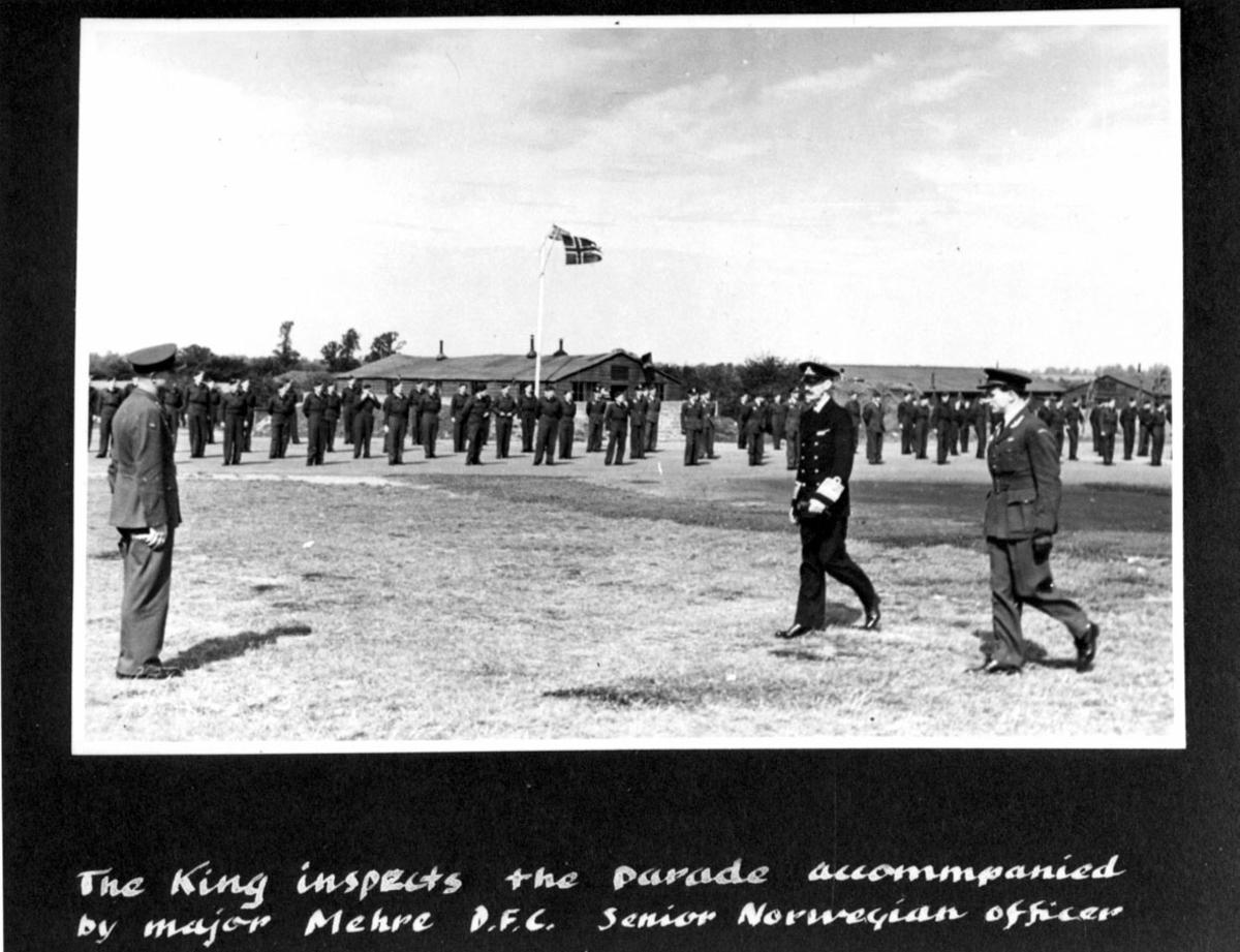 En større gruppe, i militæruniform. Militærtropp, soldater, oppstilt. Kong Haakon VII inspiserer troppen i følge med major Mehre. Håndskrevet tekst på engelsk under bildet.