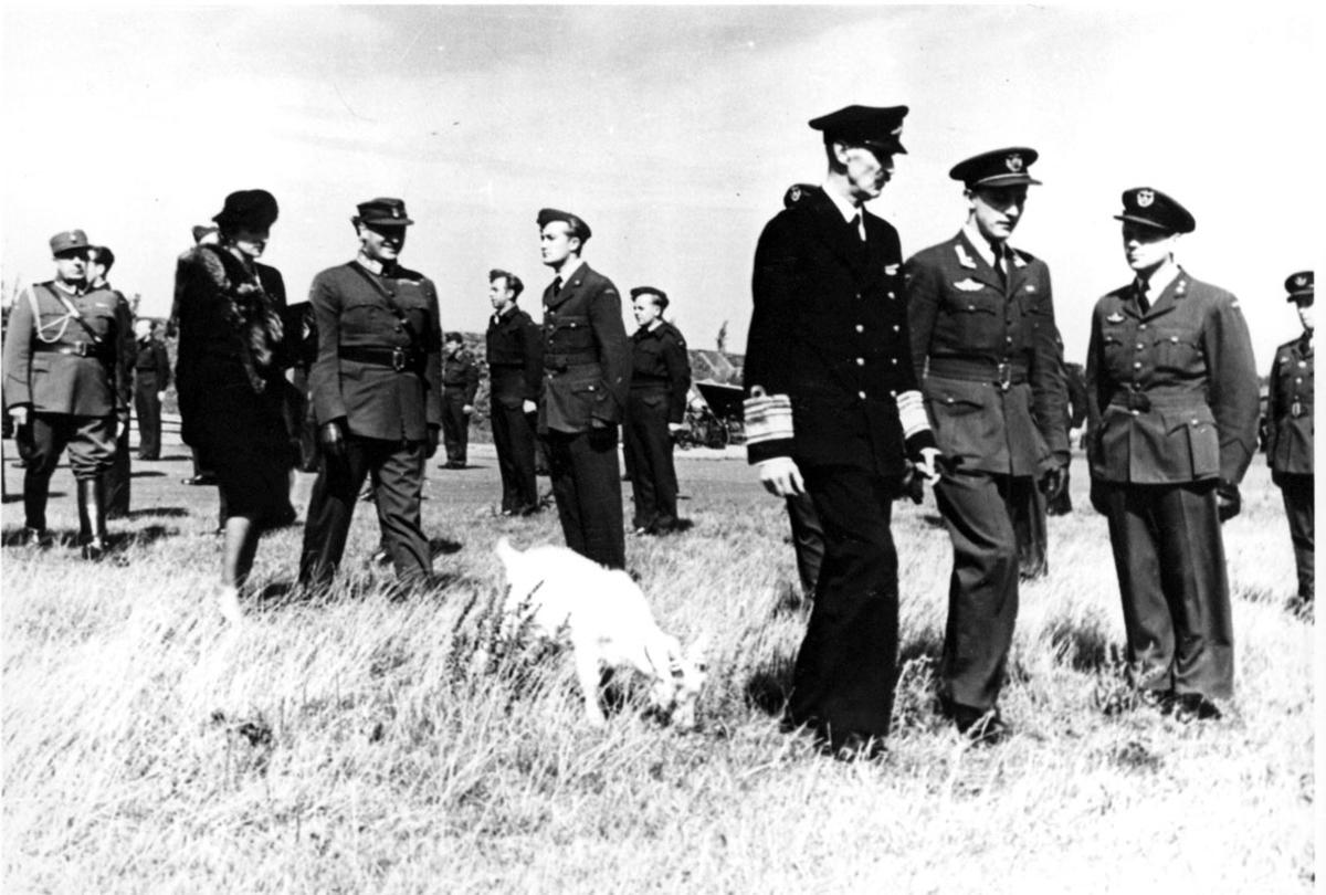Kong Haakon VII, Kronprins Olav og Kronprinsesse Märtha i følge med noen offiserer. Militærtropp, soldater oppstilt i bakgrunnen..