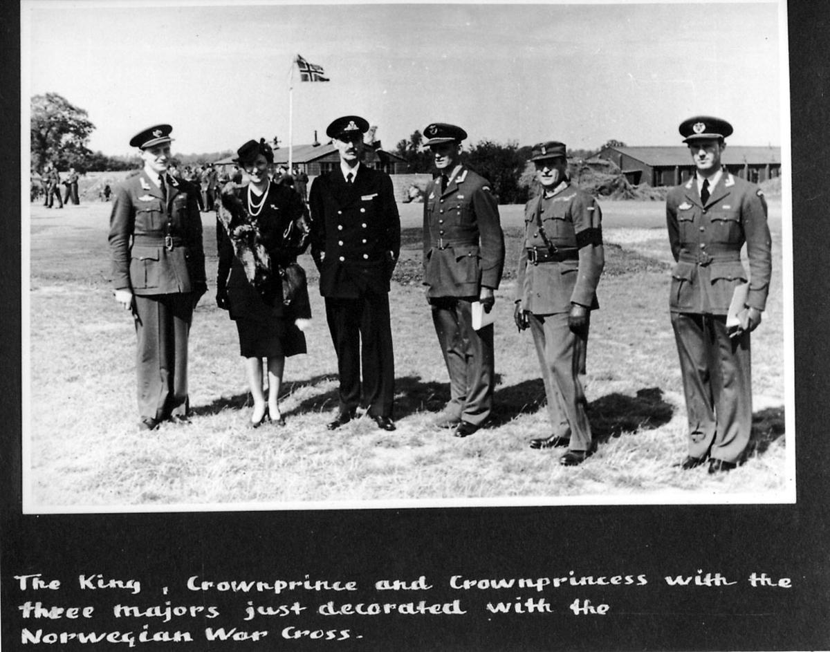 I forgrunnen, Kong Haakon VII, Kronprins Olav og Kronprinsesse Märtha, og 3 offiserer. Bak sees flere personer, soldater, i militæruniform og bygninger. Mast - stang med det norske flagg. Håndskrevet tekst på engelsk under bildet.