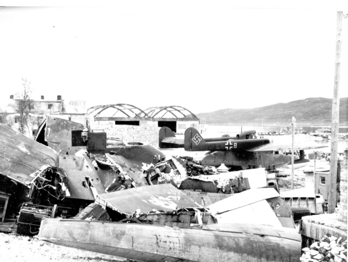 """Fly, propellfly, med """"Hakekors"""". Flydeler, vrakdeler i forgrunnen. Bygning og havneanlegg bak."""