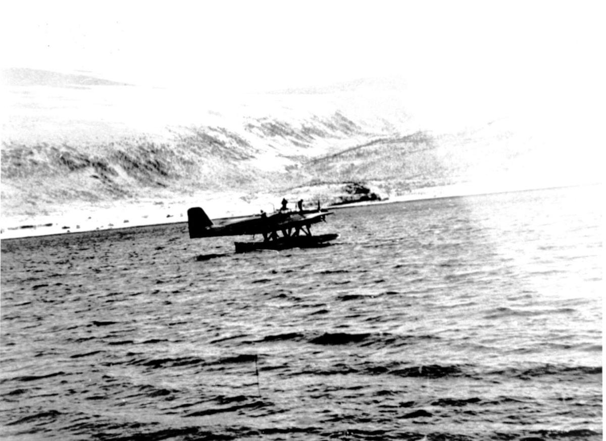 Sjøfly, propellfly, ute på fjorden. 2 personer står på flyskroget. Fjell bak.