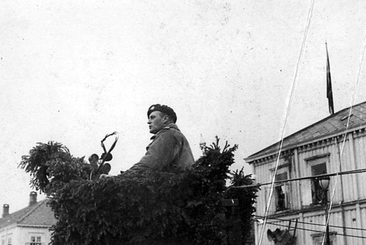Portrett, kronprins Olav på talerstol, pyntet med løv, utendørs. Bygning bak med påmonterte høyttalere.