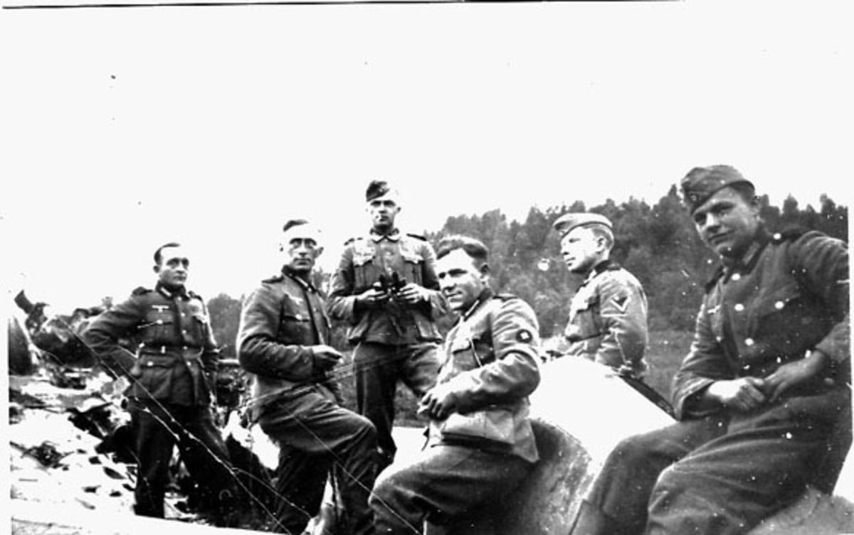 Flyhavari, nødlanding. Fly, ødelagt, på bakken bak. Flere personer i militæruniform, soldater offiserer, tyske, foran.