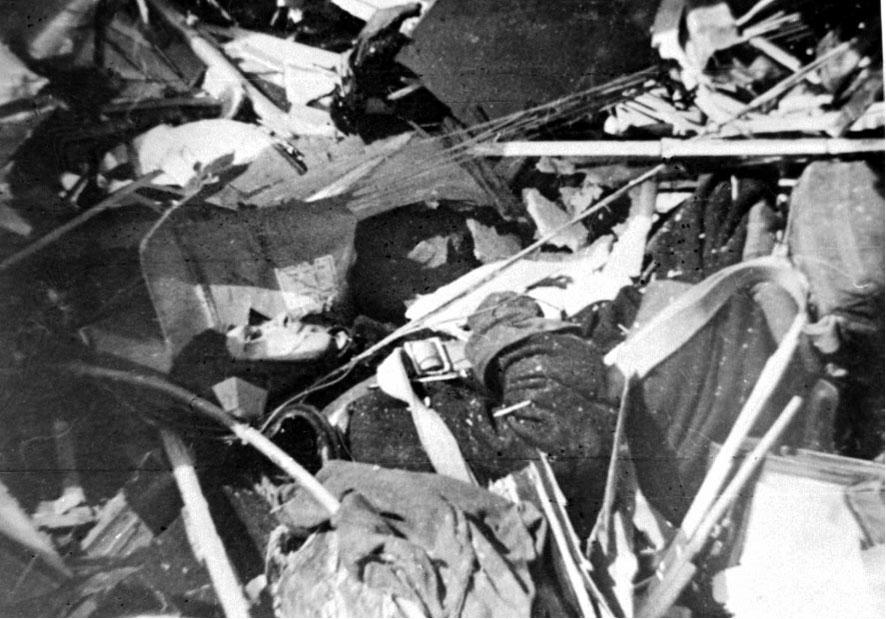 Flyvrak på bakken. Flystyrt etter nedskyting. En person i pilotuniform ligger blant flyrestene.