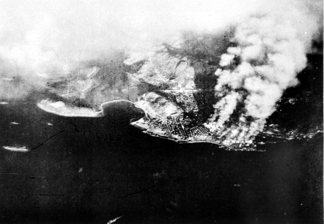 Luftfoto over tettsted ute ved kysten. Røyk stiger til værs etter bombeangrep.