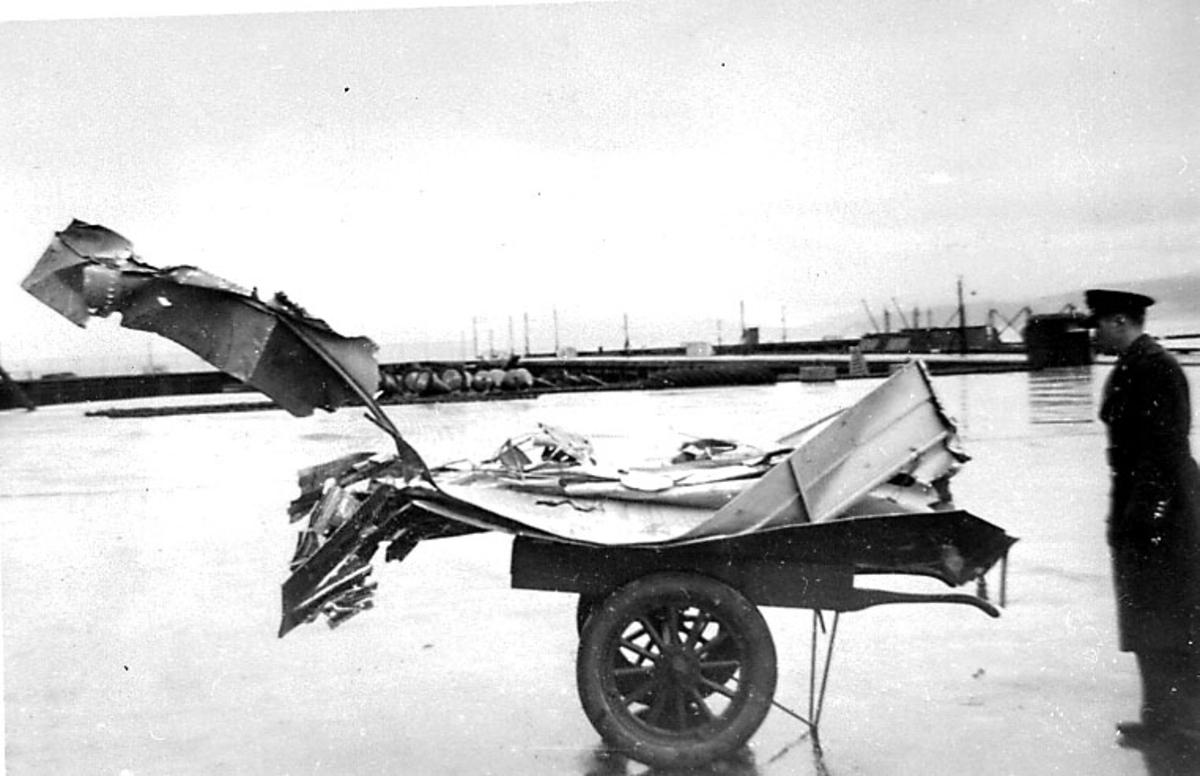 Havneområde, 1 person, militær, i militæruniform ser på ei tralle med ødelagte flydeler.