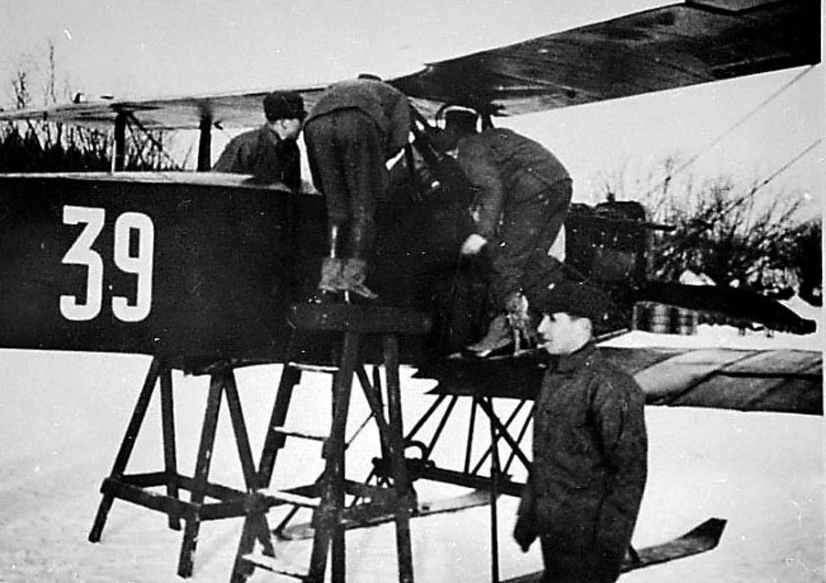 "1 fly på bakken med skiunderstell, F. F. 6 ""Kaje I"" 39 fra Hærens Flyvåpen. Flere peroner ved flyet. Forpartiet skrått fra siden. Snø på bakken."