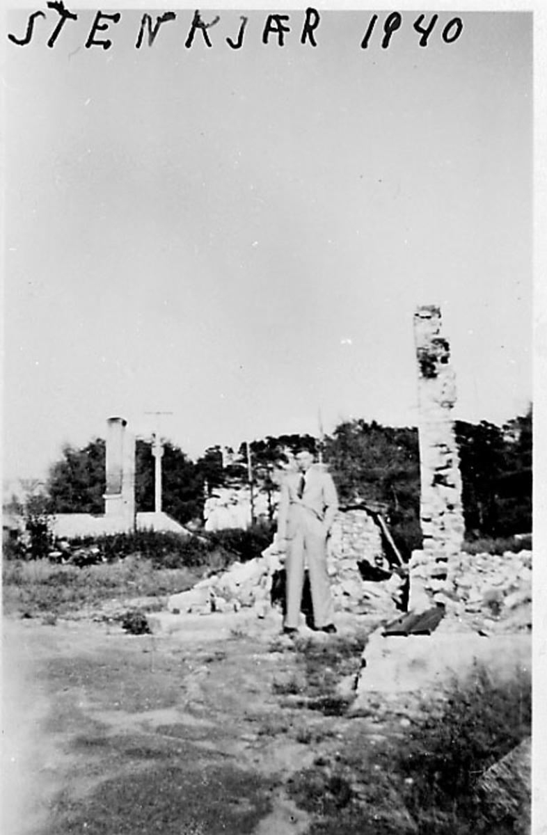 Ruiner, 1 person sitter i ruinene i forgrunnen. Steinkjær under 2. verdenskrig.