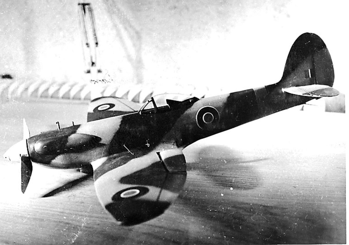 Fra album. 1 foto av modellfly, spitfire3, oppstilt på en benk.