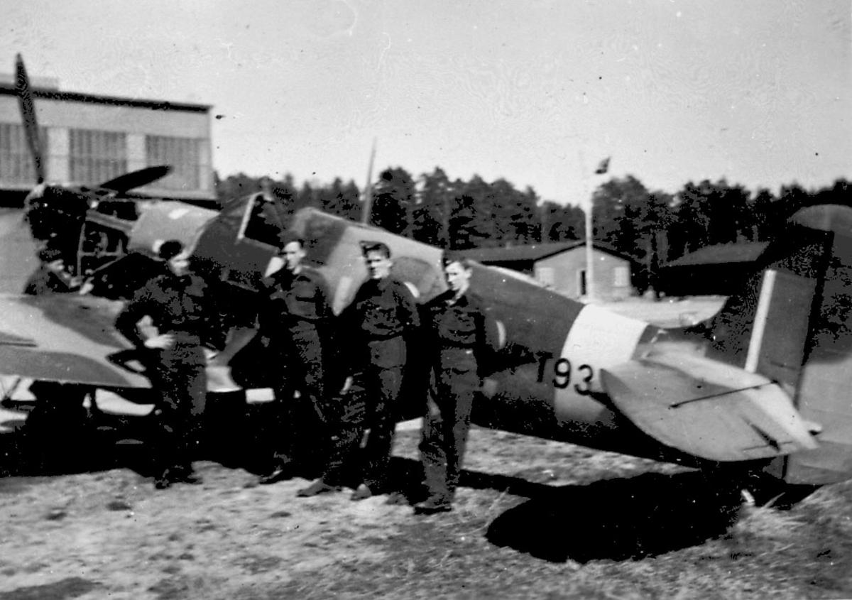 lufthavn, 1 fly på bakken, Spitfire Mk.IX Noen personer ved flyet (flypersonell). Bygning bak.