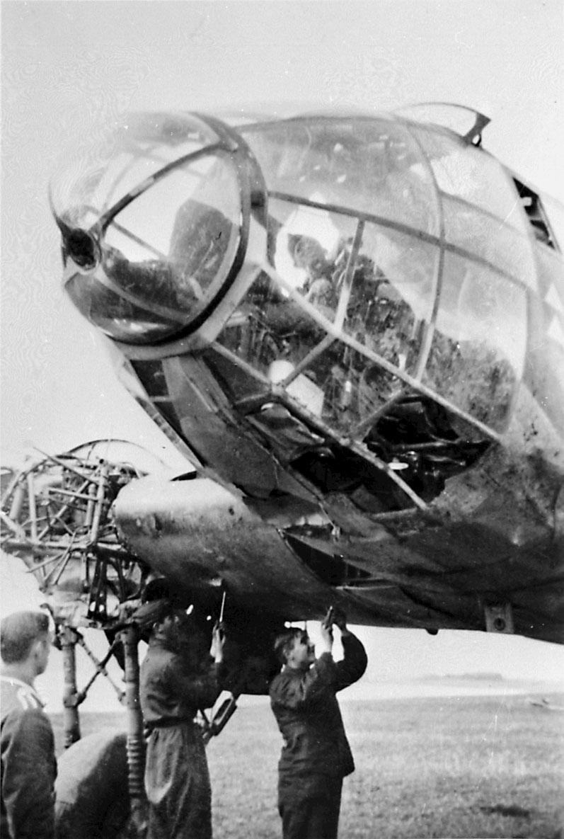 Portrett, 3 personer, tyske mekanikere jobber med å demontere ett fly, Heinkel 111, den ene av dem inne i cockpit.  1 annen person i forgrunnen.