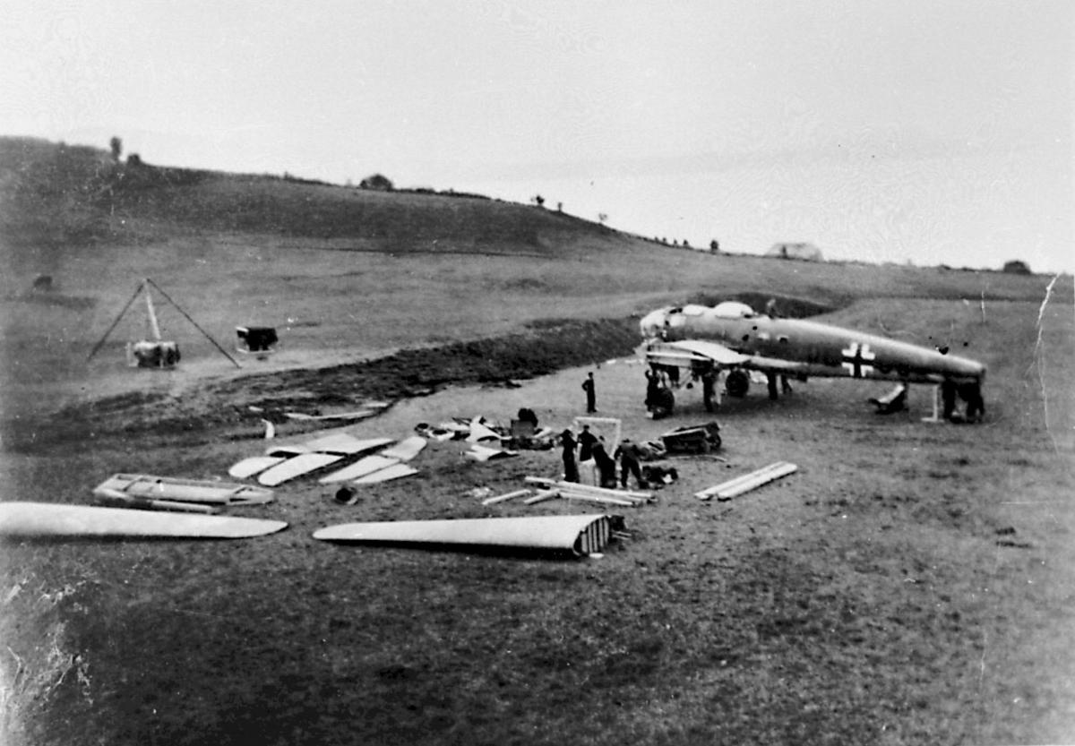 Portrett, flere personer, tyske mekanikere, står foran 1 havarert fly, Heinkel 111 under demontering av flyet.