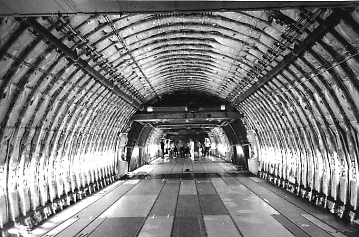 Interiørfoto på Boeing 747. Cabinen uten innredning, flere personer sees i bakgrunnen.