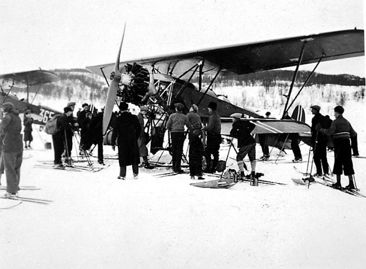 Flere personer - de fleste med ski - studeret et fly, Fokker CVD med skiunderstell, som står på bakken