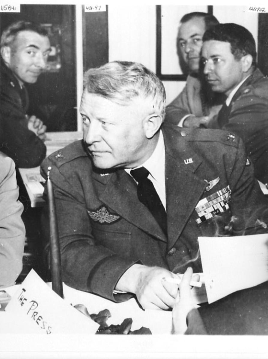 Portrett, 1 person i militæruniform sitter ved et bord. 3 andre personer som står i bakgrunnen. Tatt innendørs.