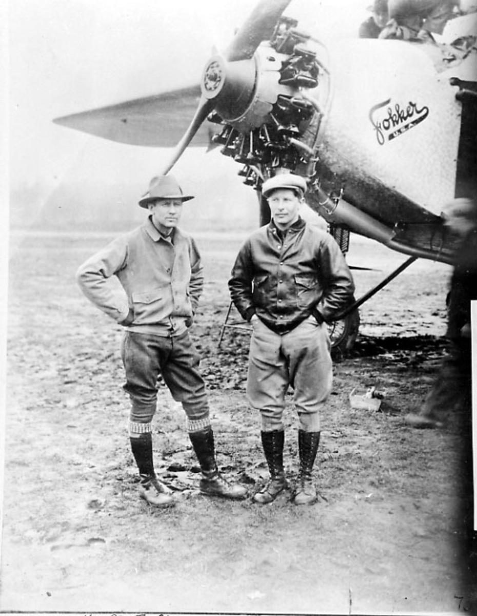 Portrett, 2 personer står foran nesepartiet på et fly - Fokker -. Tatt utendørs