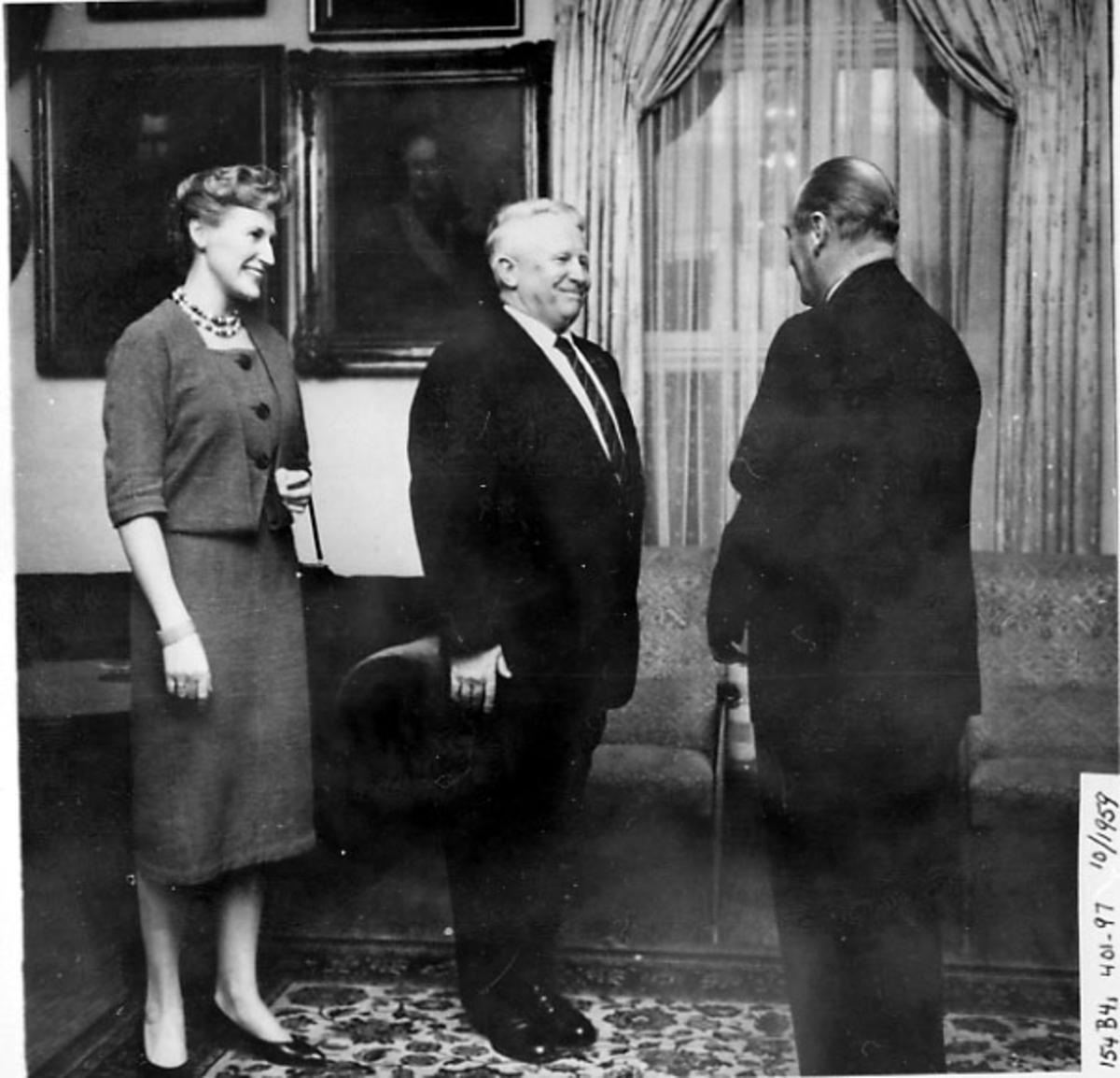 Portrett, 3 personer iført finklær. Tatt innendørs. Bernt Balchen hilser på Kong Olav V.