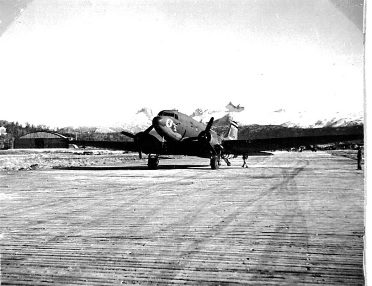 Lufthavn, 1 fly på rullebanen. Fjell bak. C-47 Dakota