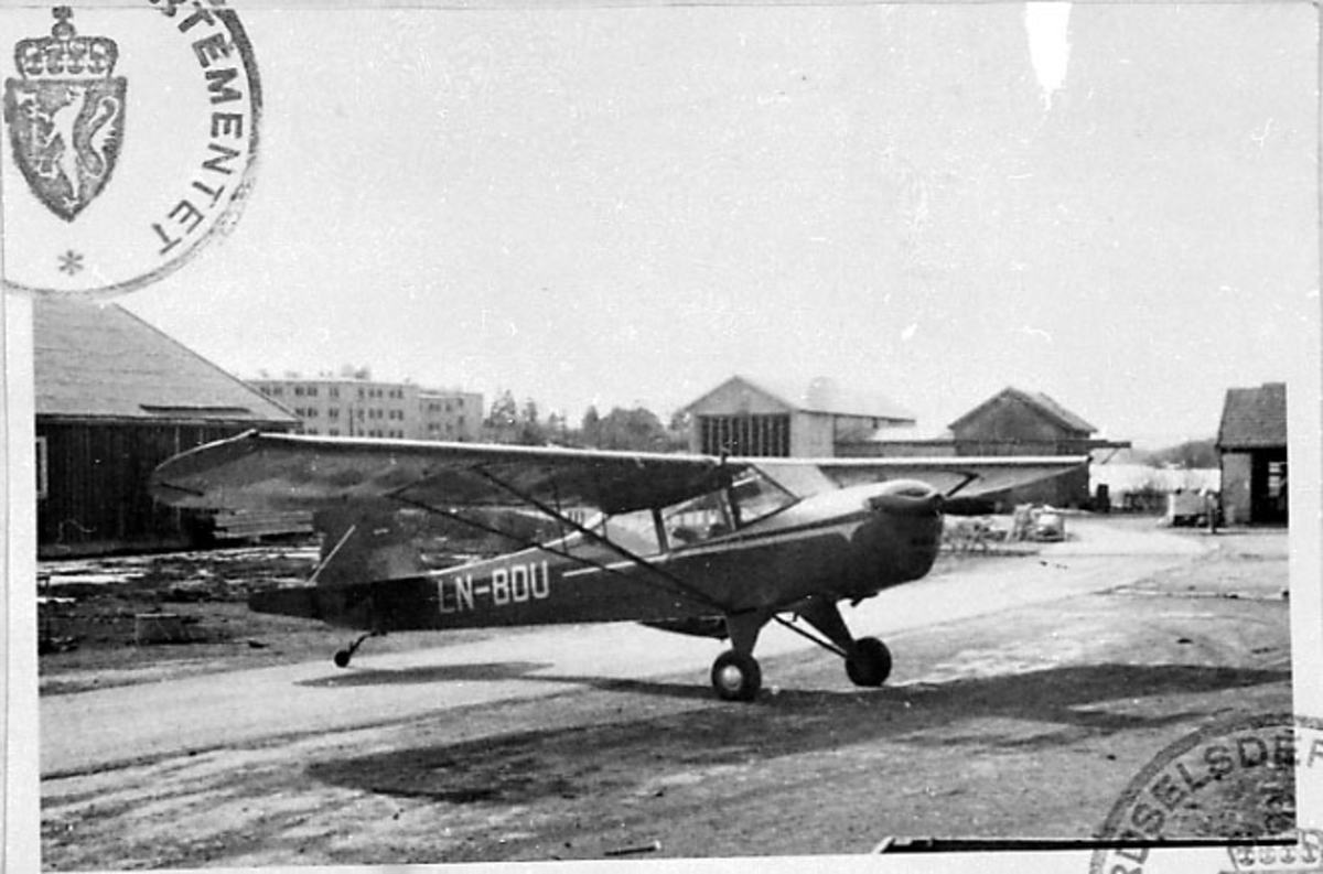 1 fly på bakken, Auster 5, LN-BDU, fra A/S Norrønafly. Bygninger bak.