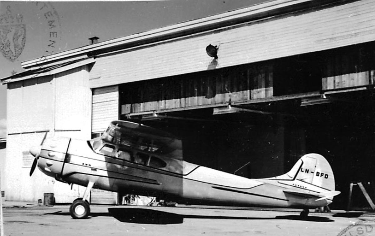 1 fly på bakken, Cessna 195 B, LN-BFD, fra Thor Solberg Aviation A/S. Bygning/hangar bak.