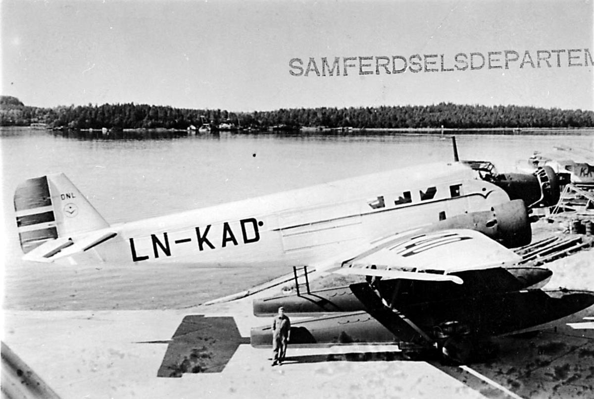 "Sjøflyhavn, 1 sjøfly står på land, Junkers JU 52 3mg g8e, LN-KAD ""Per"" fra DNL A/S Oslo. 1 person foran flyet."