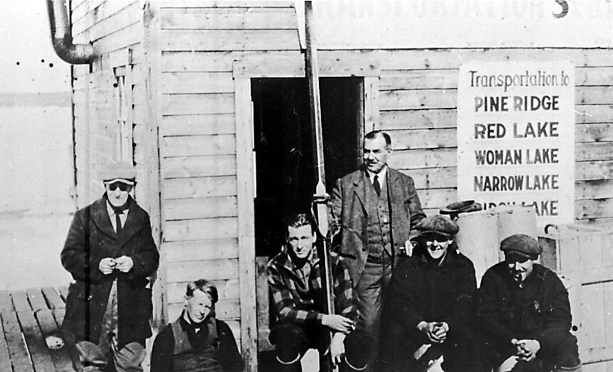 Portrett. 4 personer foran lita bygning/hytte.  Portrett: Blant annet Bernt Balchen. Påskrift på bygningen: Transportation to Pine Ridge, Red Lake, Woman Lake, Narrow Lak.