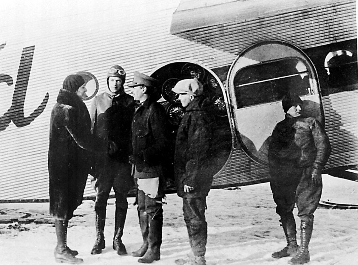 """Portrett. 5 personer foran 1 fly, Ford. Snø på bakken. 1 kvinne hilser på """"flymannskapet. Ant fra Byrds antarktiskekspedisjon med flyet """"Ford"""""""
