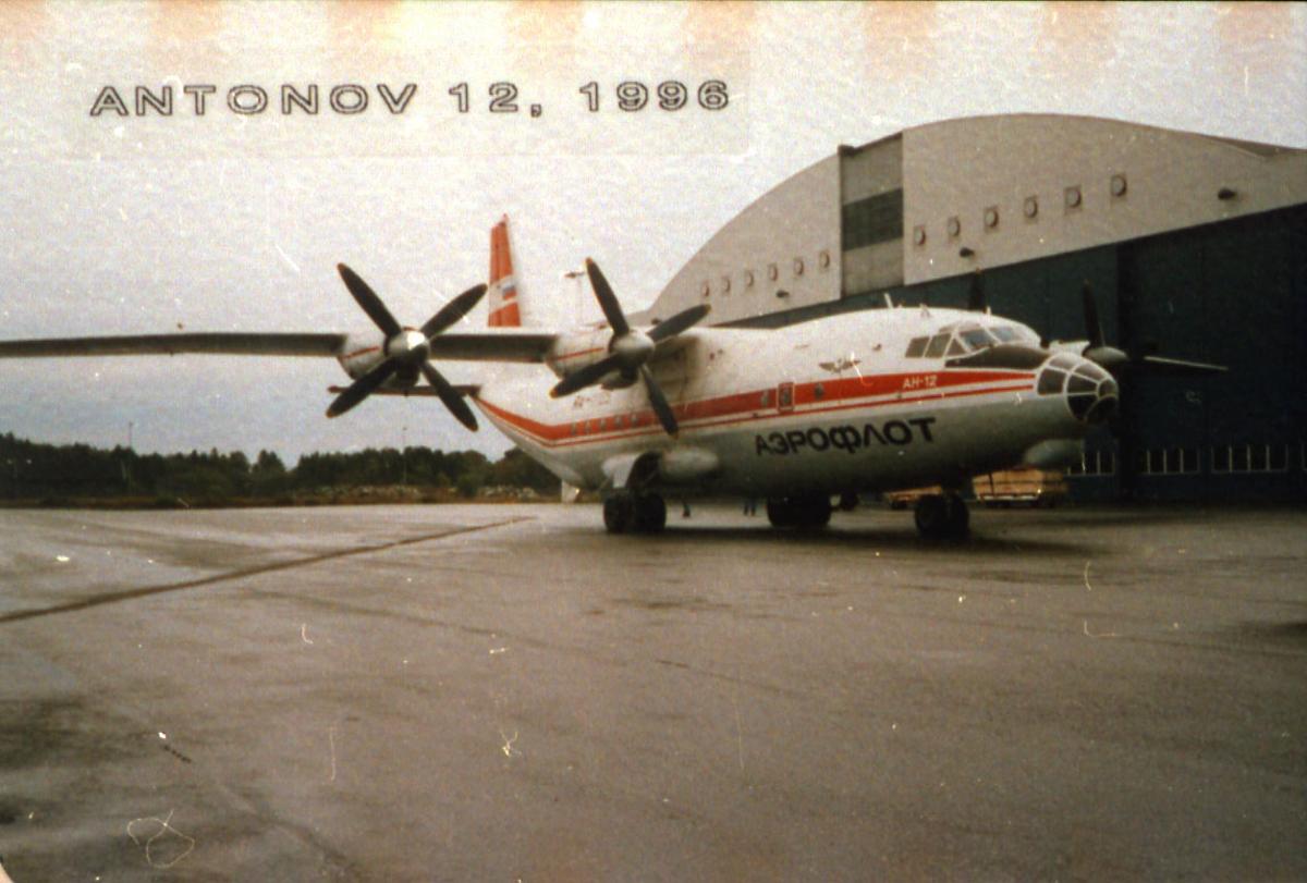 Lufthavn, 1 fly på bakken, Antonov AN-12, RA-11105 fra Aeroflot. Står ved siden av hangarbygning.