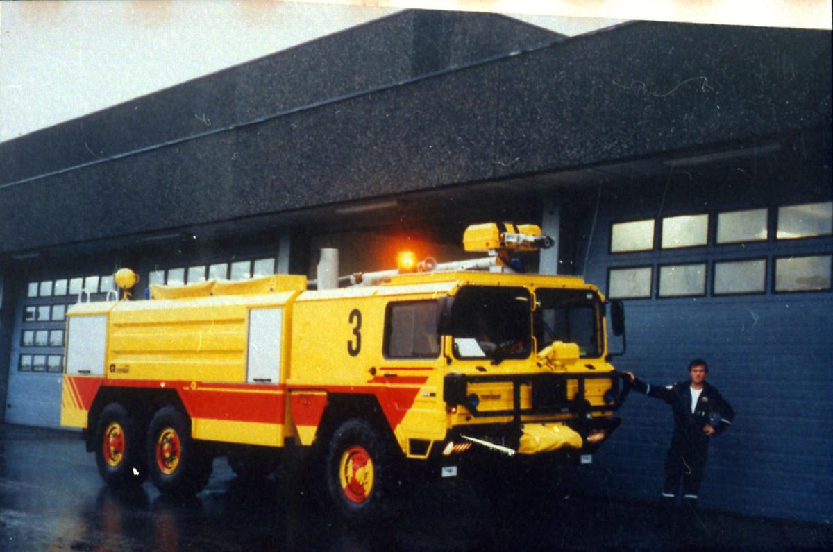 Lufthavn, 1 kjøretøy, brannbil, ved siden av garasjebygning