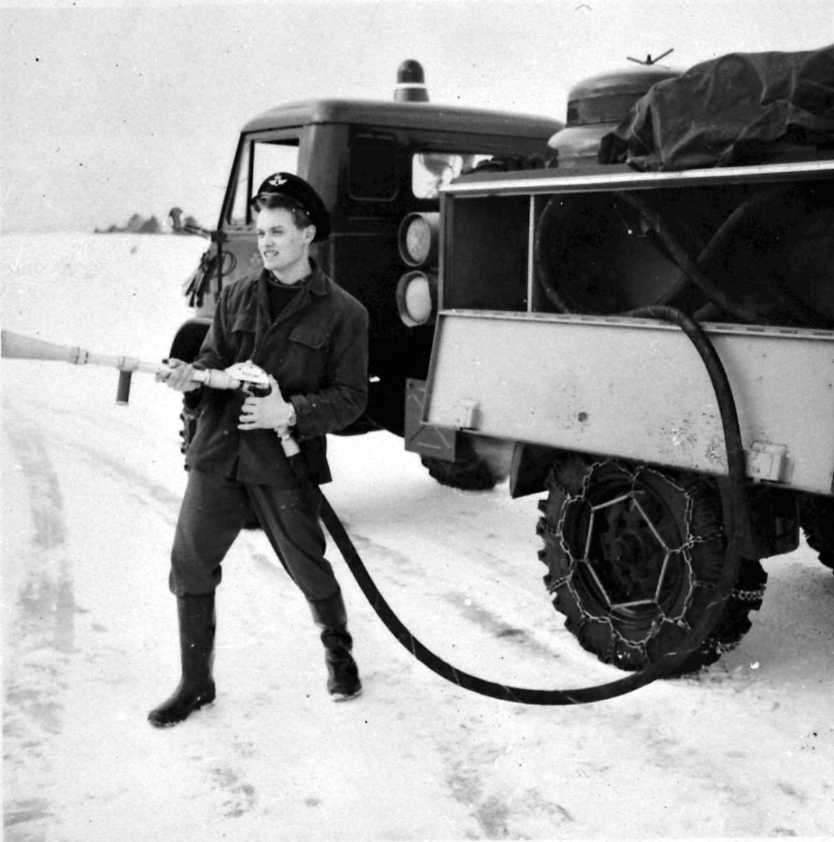 Lufthavn, 1 Større kjøretøy, brannbil. Portrett 1 personer i uniform, står og betjener vannslange fra brannbilen. Snø på bakken.