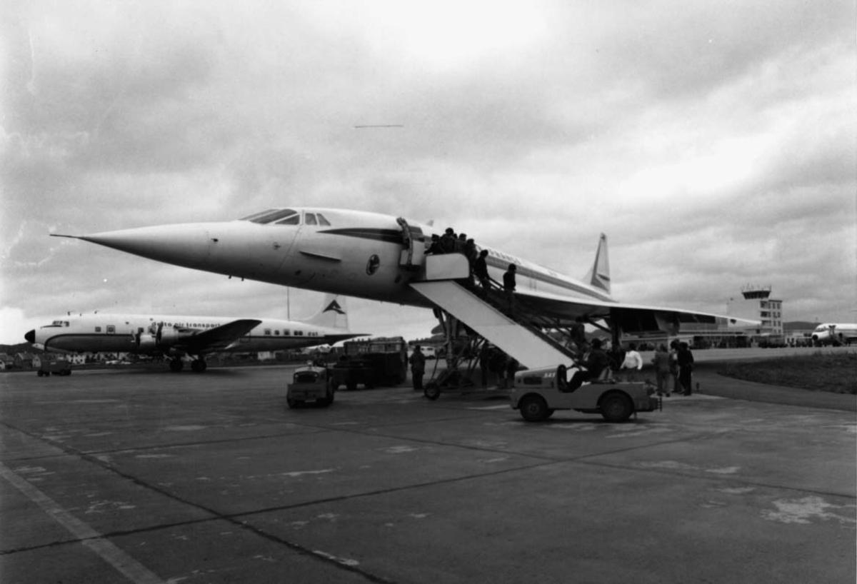 Lufthavn, to fly på bakken. I forgrunnen Concorde F-WTSB fra Air France. Flere kjøretøyer og personer ved flyene.