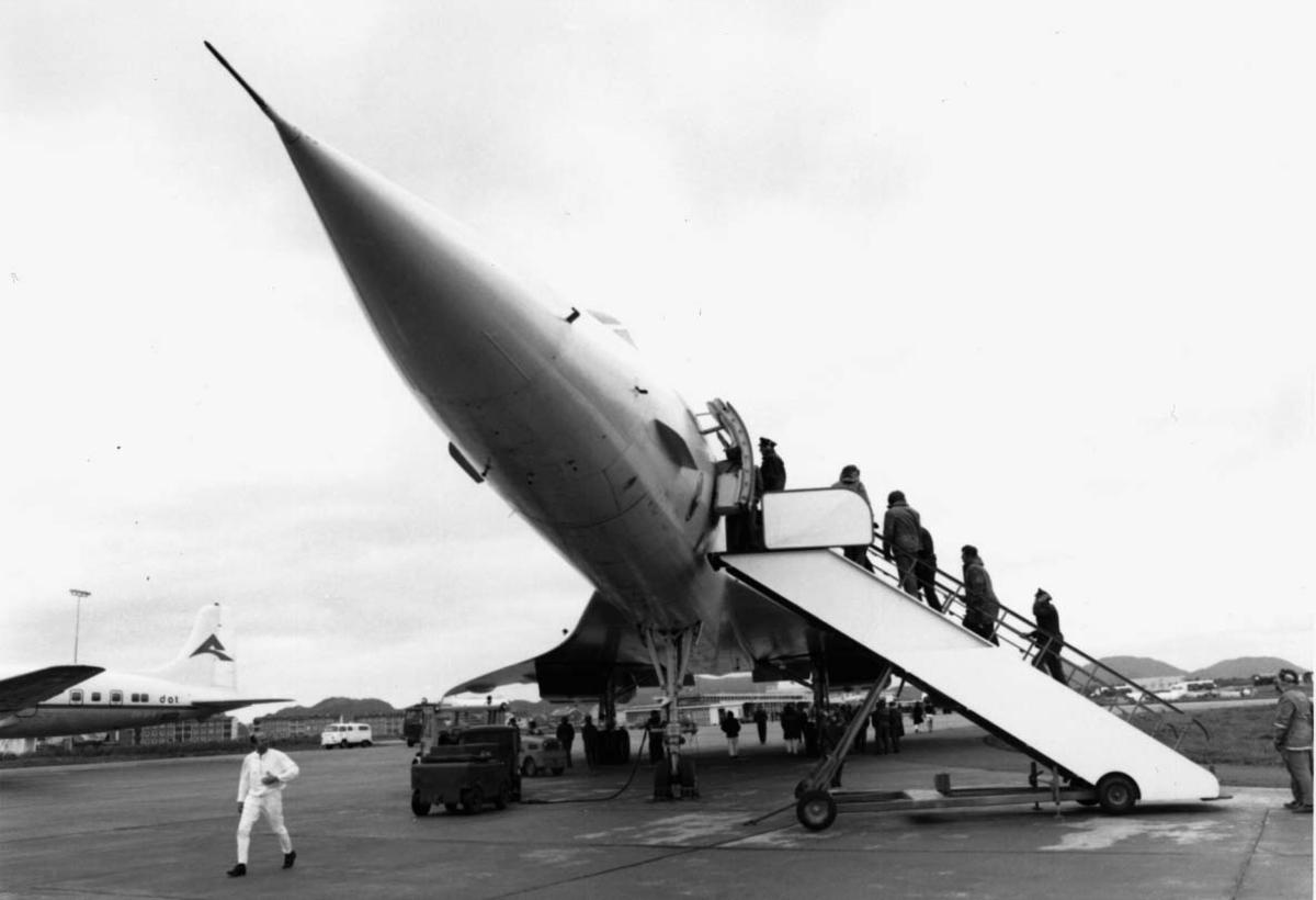 Lufthavn, 1 fly på bakken Concorde F-WTSB fra Air France. Noen persone/passasjerer på vei inn i flyet. Annet fly i bakgrunnen.