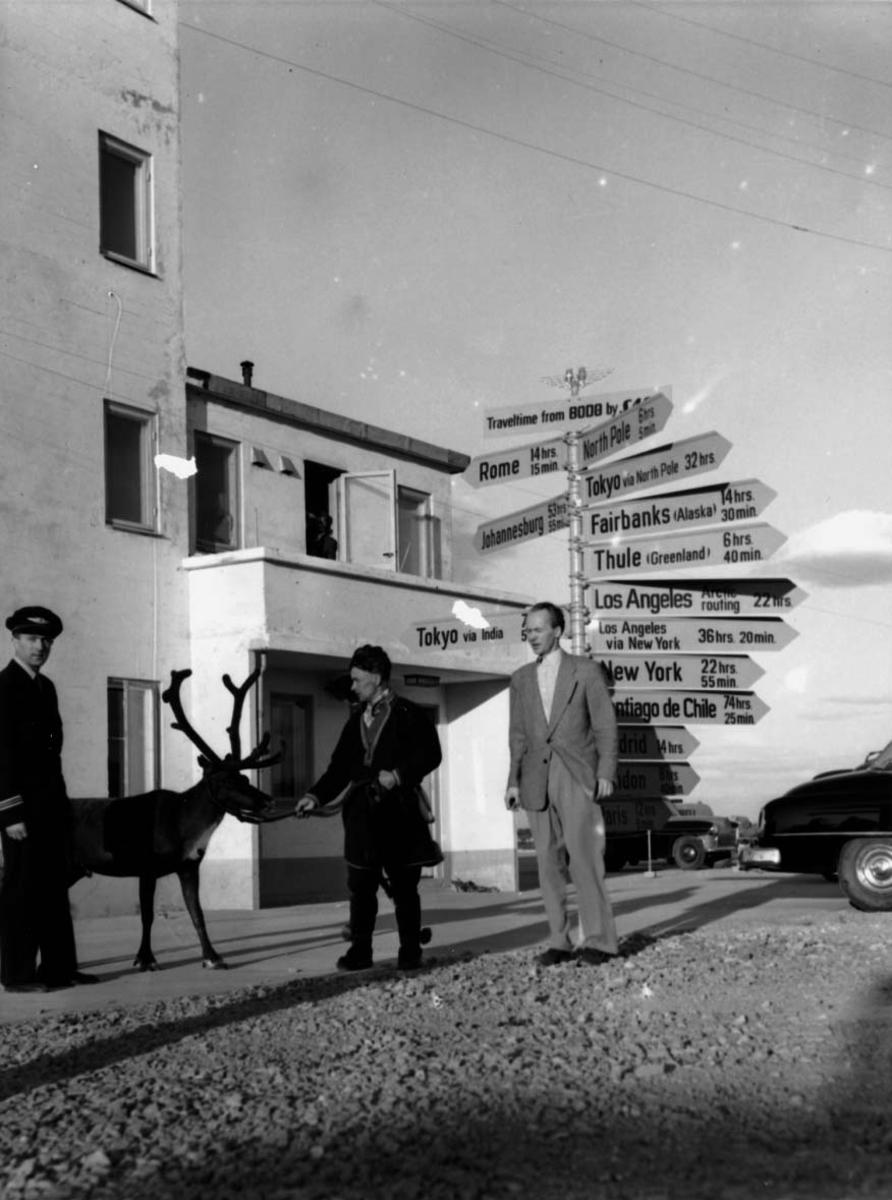 Lufthavnt, tre personer ved ett skilt som viser flyruter foran ei bygning. En av personene en same med kjørerein