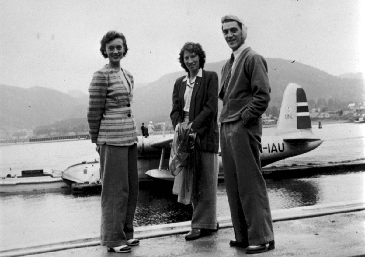 """Portrett, 3 personer på kaia foran 1 fly, Short S.25 Sunderland LN-IAU """"Bamse Brakar"""" fra DNL."""