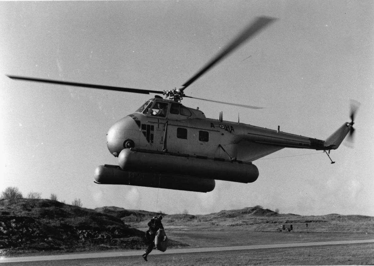 Lufthavn - flyplass. Ett helikopter Sikorsky H-19  Chickasaw  A-HA like over bakken. En person med en redningsflåte henger i en line - vaier fra helikopteret.