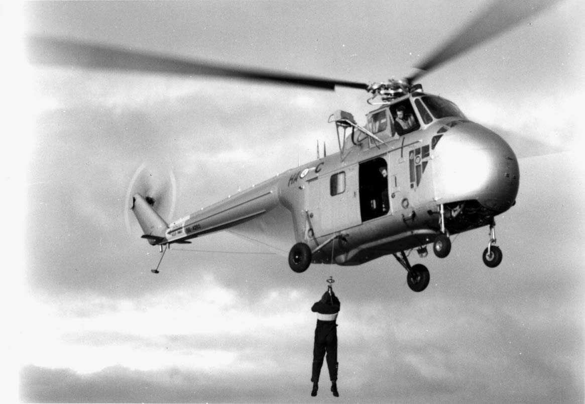 Lufthavn - flyplass. Ett helikopter Sikorsky H-19  Chickasaw   HA-C  like over bakken. En person henger i en line - vaier fra helikopteret.