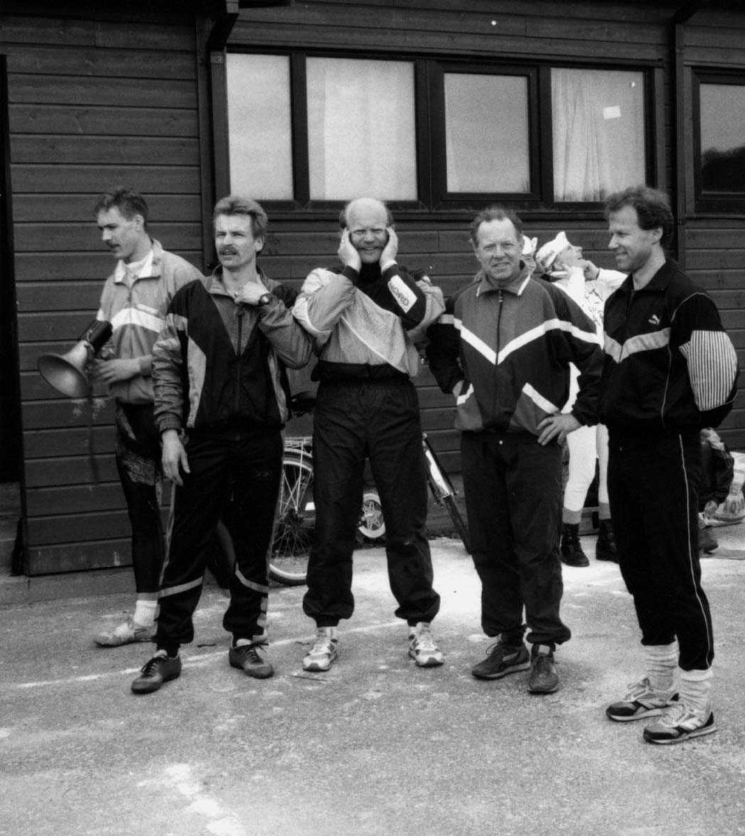 Gruppe.  Fem personer i idrettsantrekk utenfor en bygning.