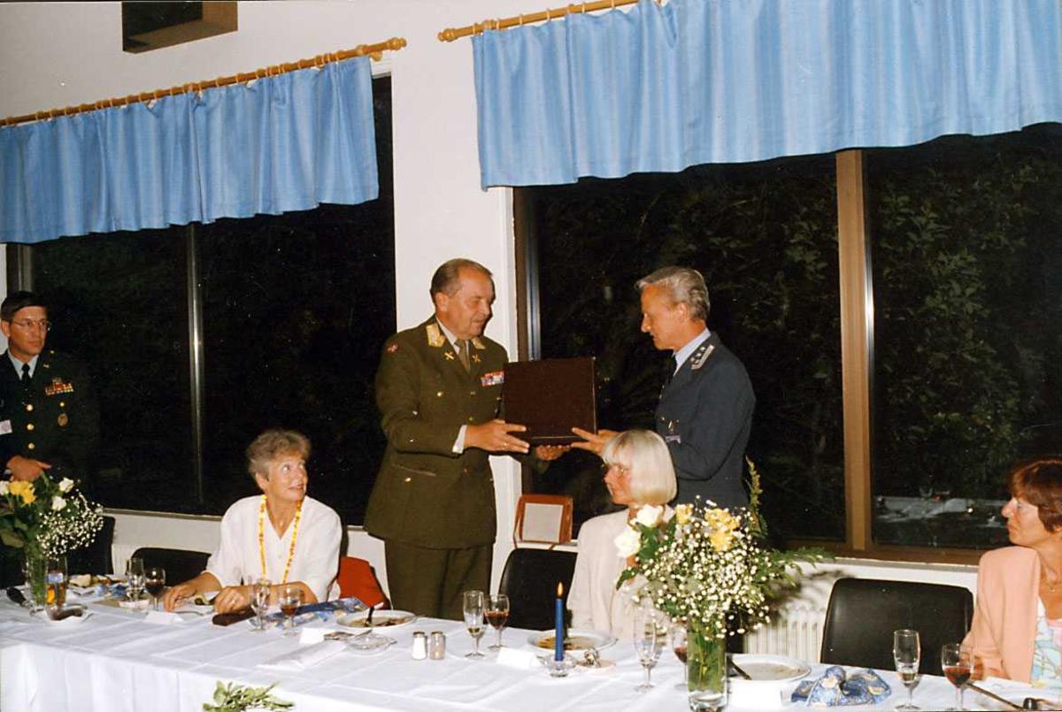 Gruppe.   Seks personer ved et bord, gaveoverekkelse ØKN-Stasjonssjef.