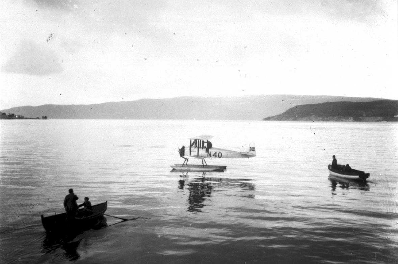 1 fly ligger stille på havoverflata, Sääski, N40. 2 åpene båter med noen personer ombord, ant. tilbringerbåter.