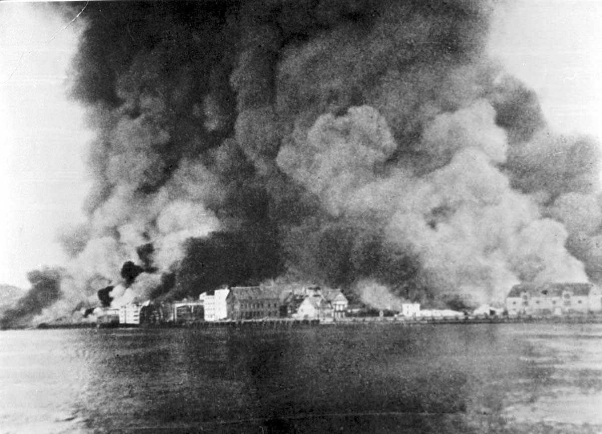 Bygninger i brann, mye røyk. Havneområde i forgrunnen