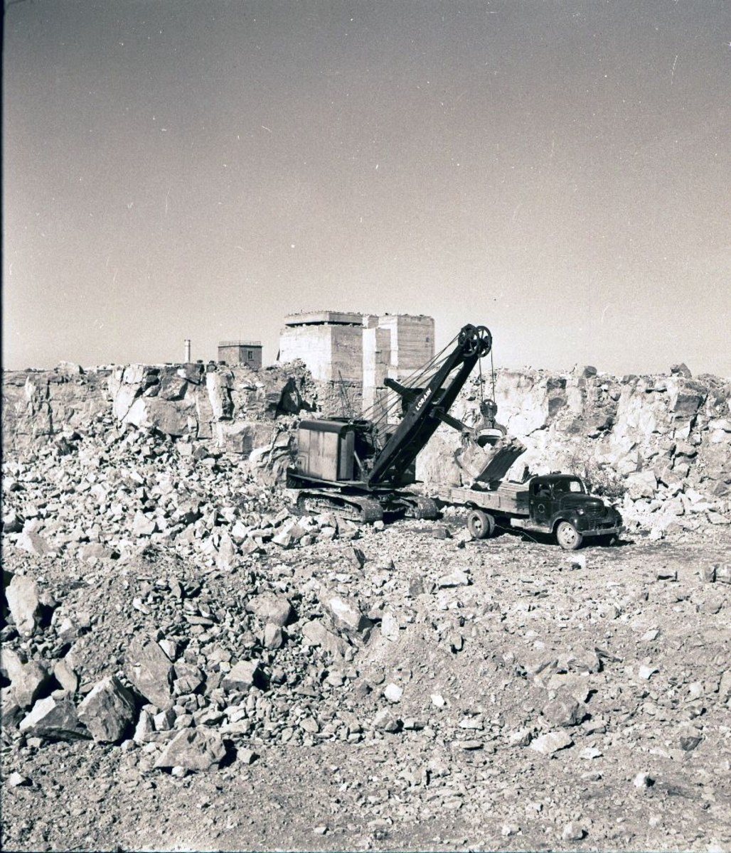 Landskap. Fra byggingen av Bodø Flyplass. En lastemaskin på belter fyller en lastebil med steinmasser.