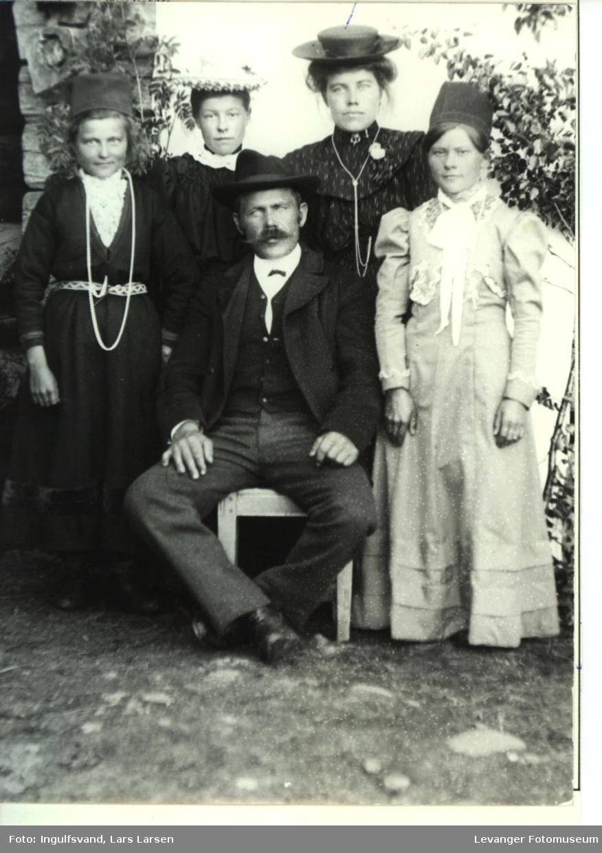 Gruppebilde av en mann og tre kvinner, en av kvinnene ført samiske kllær og en samisk hodebekledning.