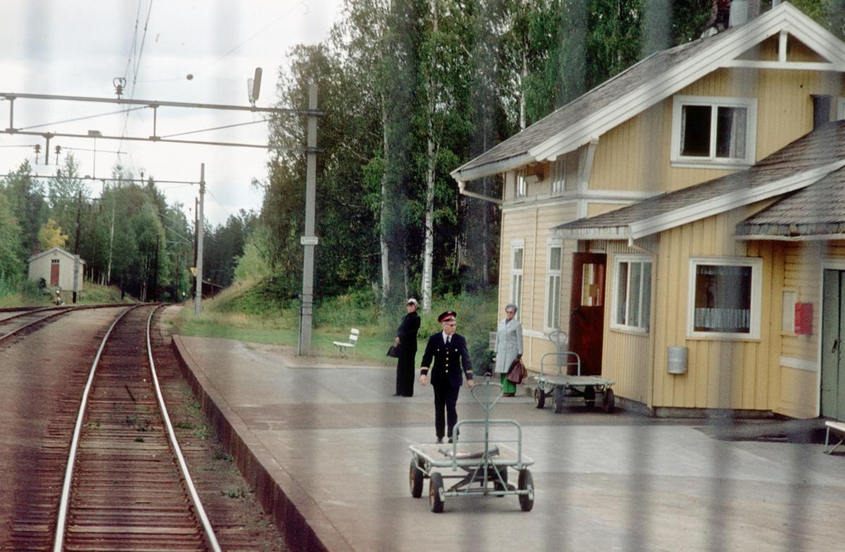 Persontog fra Oslo Ø kjører inn på Nygard stasjon, sett fra lokomotivet. Togekspeditør på plattformen og reisegodstralla står klar. Et par reisende til Gjøvik venter på toget.
