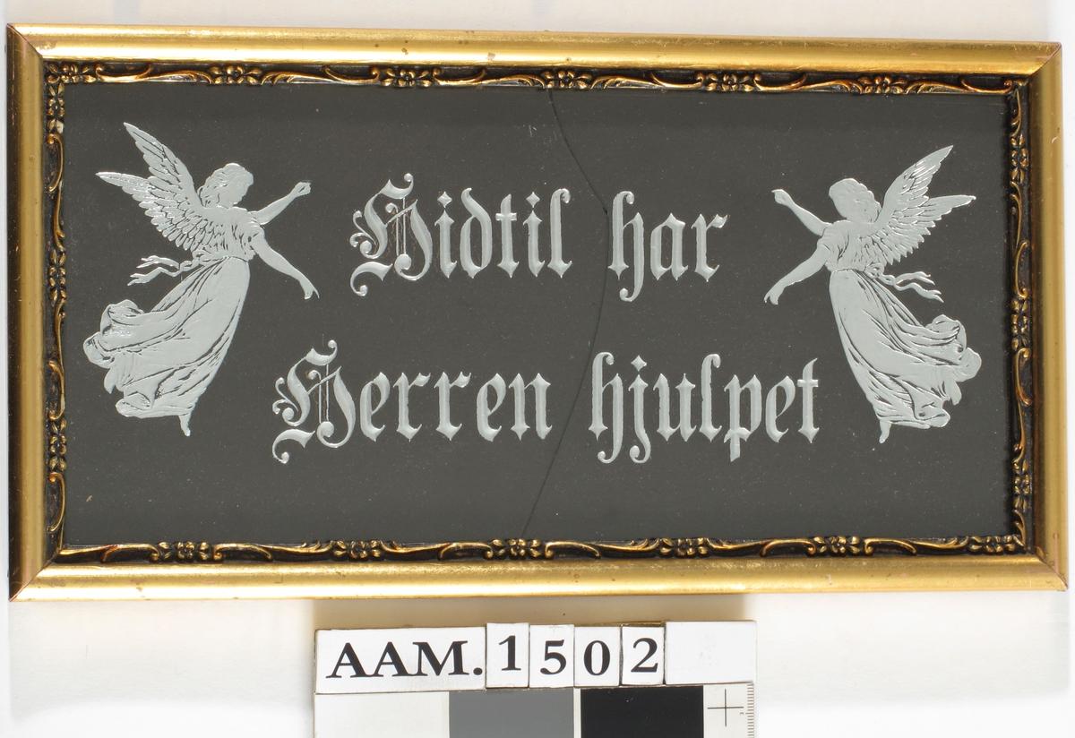Skriftsted :  Hidtil har Herren hjulpet.   Grå/sort kartong med ned presset   og sølvbelagt tekst.   Ramme enkel forgylt list, innenfor denne en smal ranke   i gull på sort bunn.