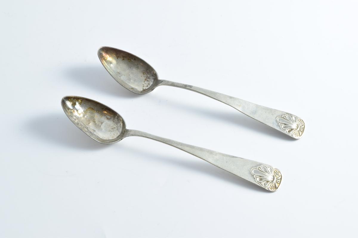 To teskjeer i sølv med dekor i form av en støpt pamlett på øverste del av skaftet.