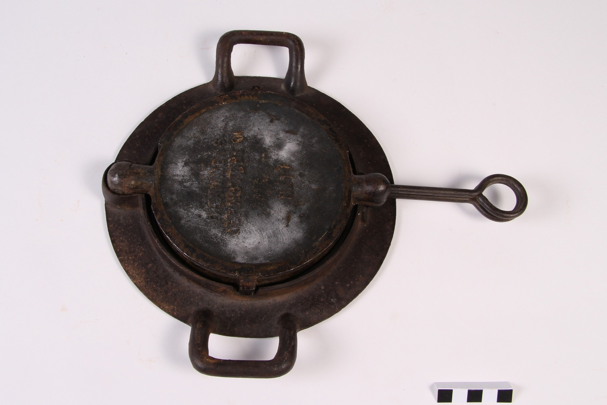 Krumkakejern til vedkomfyr. Krumkakejernet ligger i en jernring og kan snus.