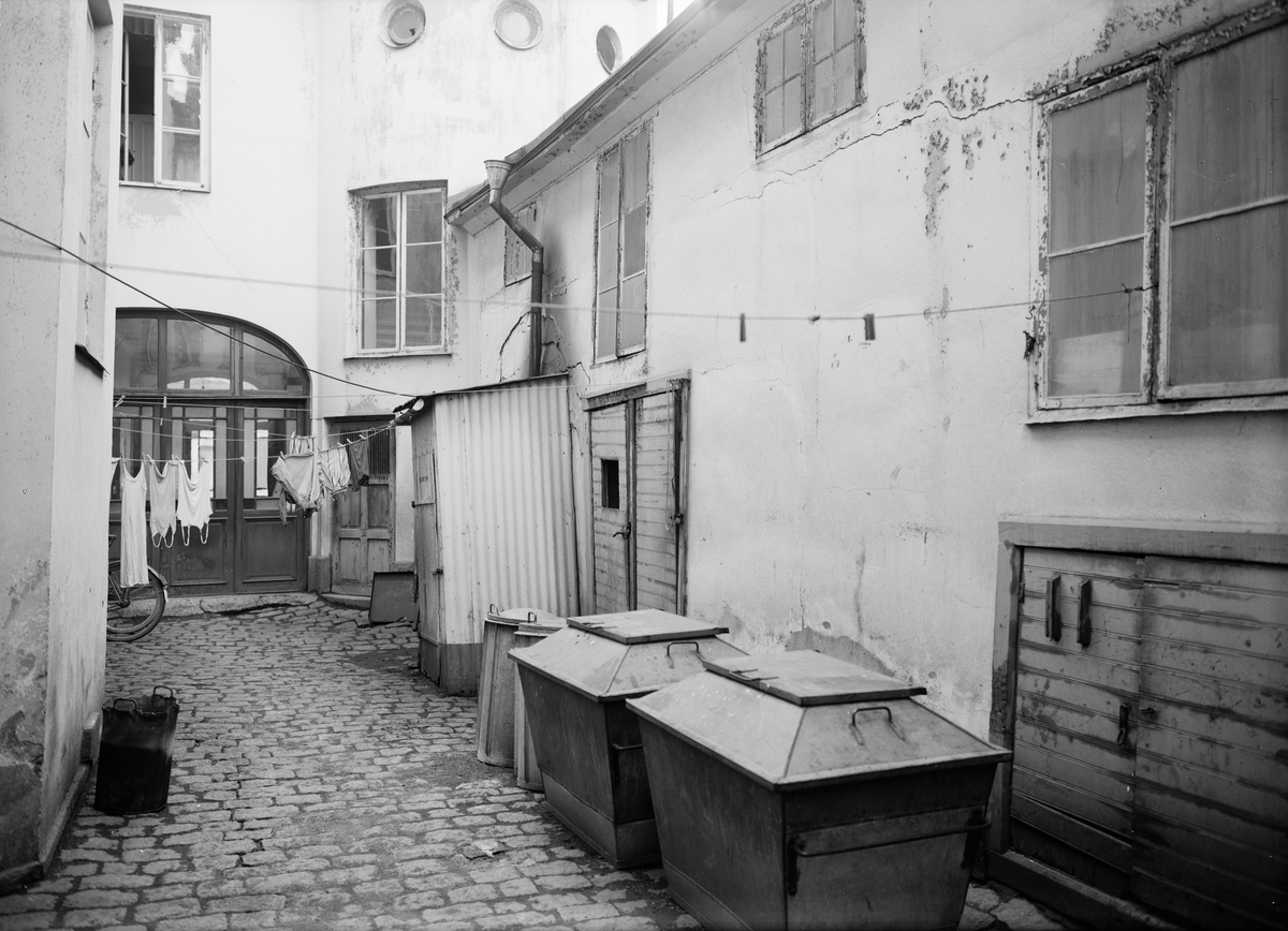 Gårdsinteriör med soptunnor och tvätt på tork, Uppsala 1944