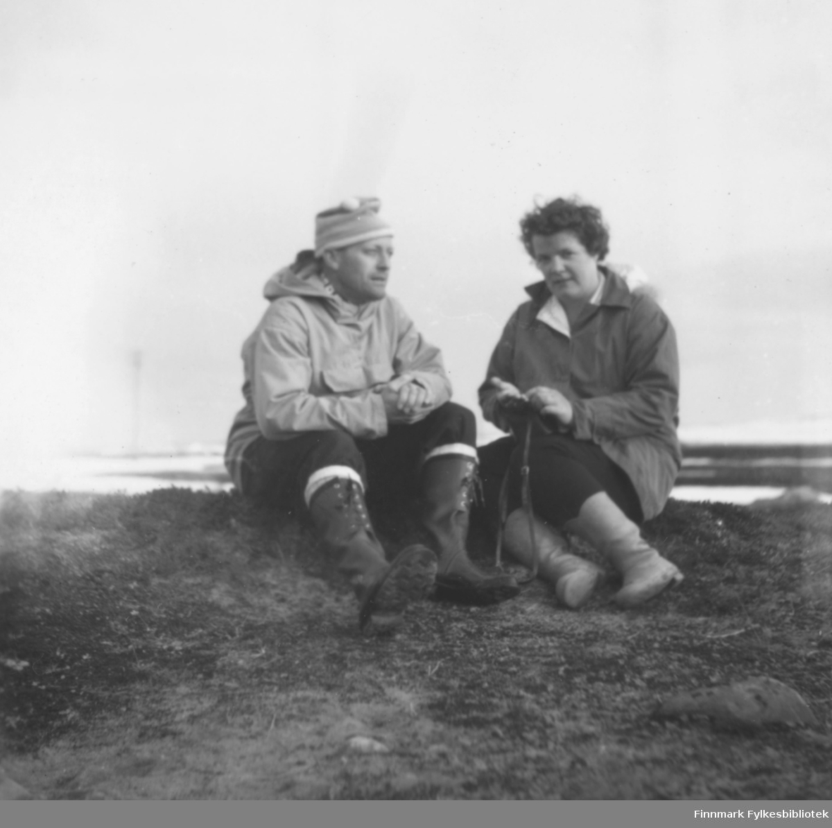 På tur, antakelig i Skallelv, ca. 1961-1963. Fritz og Ragnhild Ebeltoft sitter på en bar rabbe. Det ser ut til å være på vårparten, det ligger ganske mye snø i bakgrunnen